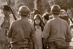 A young female protester wearing a helmet faces down helmeted and armed police officers at an anti-Vietnam War demonstration outside the 1968 Democratic National Convention, Chicago, Illinois, August 1968. (Photo by Hulton Archive/Getty Images)